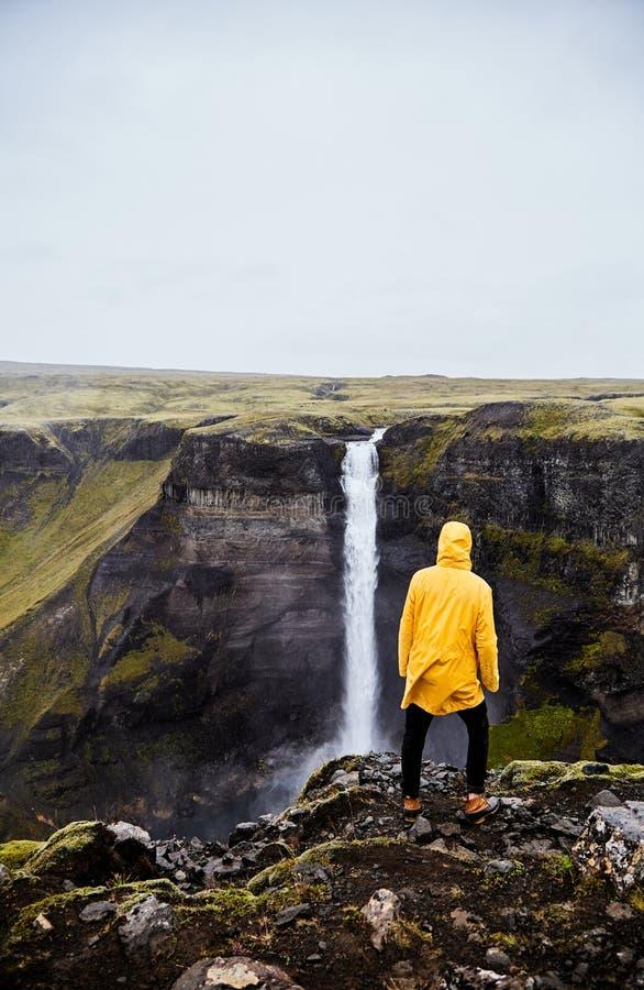 Vattenfall Haifoss i Island En ung grabb står på en klippa och ser vattenfallet arkivbild