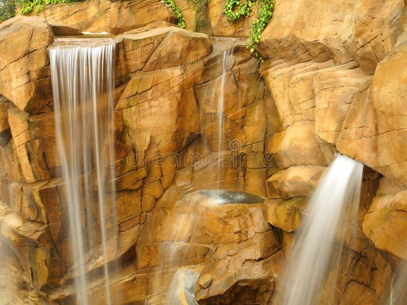 Vattenfall på bakgrundsinställningen för brant klippa arkivbild