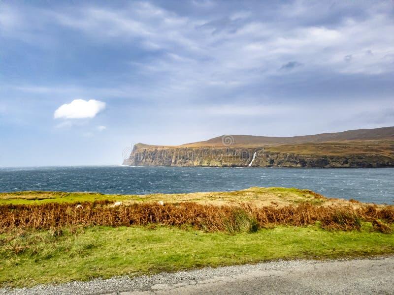 Vattenfall på vänstersidan som stoppas och vändas om av höststormen Callum på de sedda klipporna från lägre Milovaig - ö av Skye royaltyfri fotografi