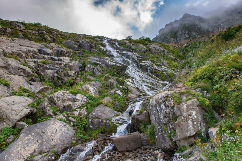 Vattenfallet för det Kaukasus berget vaggar på berget i den gröna steniga bergssidan arkivbild