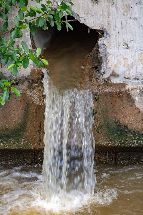 Vattenflöden från ett stort hål i väggen arkivfoton