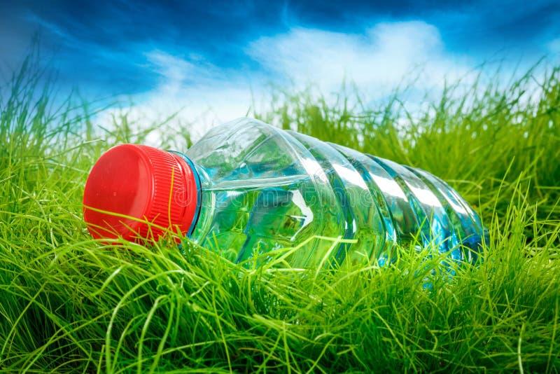 Vattenflaska på gräset. arkivbild