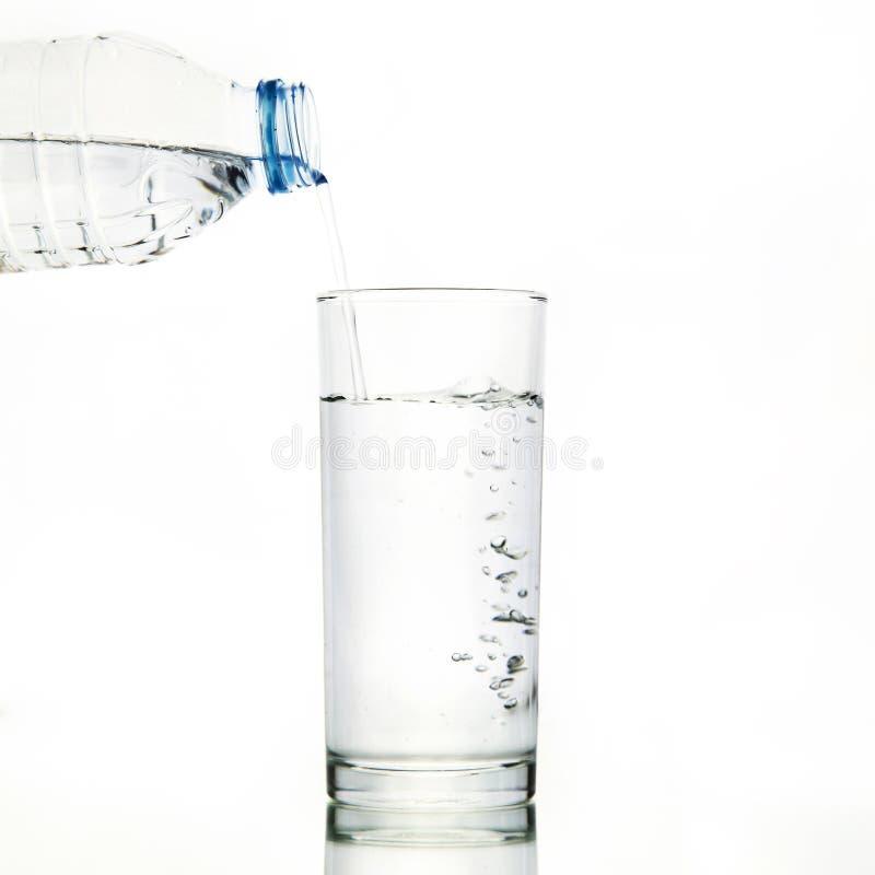 Vattenflaskan häller vatten till exponeringsglas royaltyfri foto
