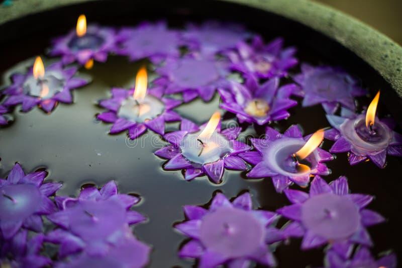 Vattenhandfatstil och blommastearinljus arkivfoton