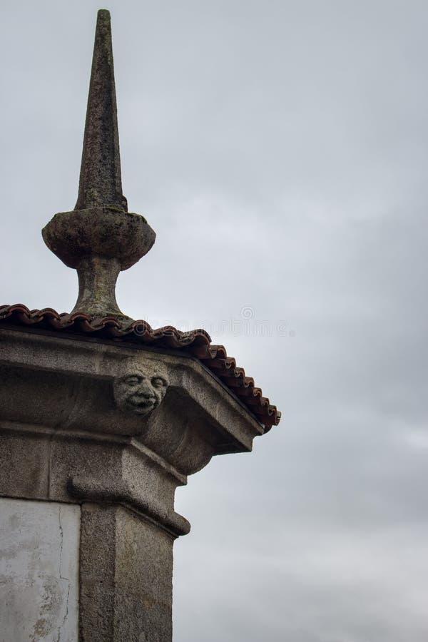 Vattenkastareskulptur på medeltida kyrklig tornspira mot molnig himmel Forntida begrepp för gotisk arkitektur Vattenkastareframsi royaltyfria foton