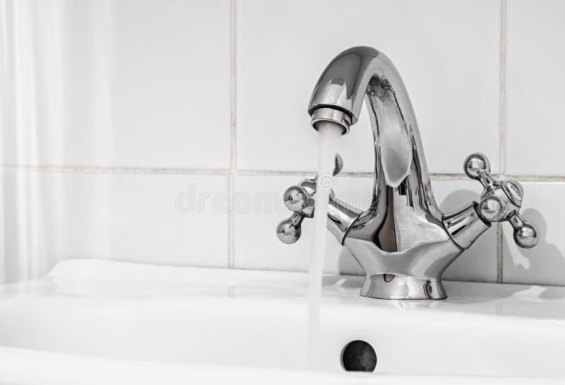 Vattenklapp med en vattenström i badrummet royaltyfria bilder