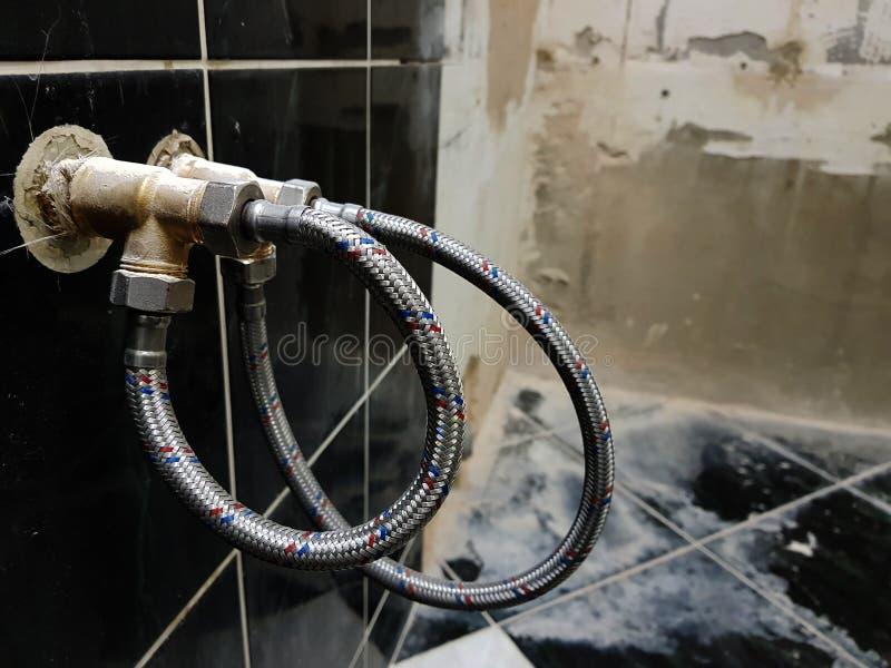 Vattenkran och böjlig anslutning för vattenförsörjning - klappvatten fotografering för bildbyråer