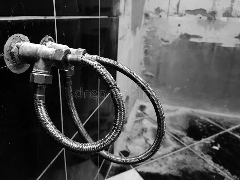 Vattenkran och böjlig anslutning för vattenförsörjning - klappvatten arkivbild