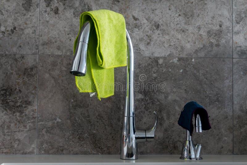 Vattenkran och filtrerat vattenklapp med microfibretorkdukar och grå backsplash för marmorstentegelplatta arkivbilder