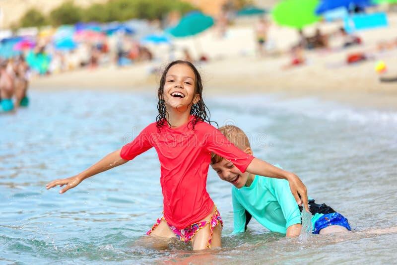Vattenlek med två lyckliga barn som har gyckel på stranden, kamratskapbegrepp med att le pojken och flickan som tillsammans tycke royaltyfri foto