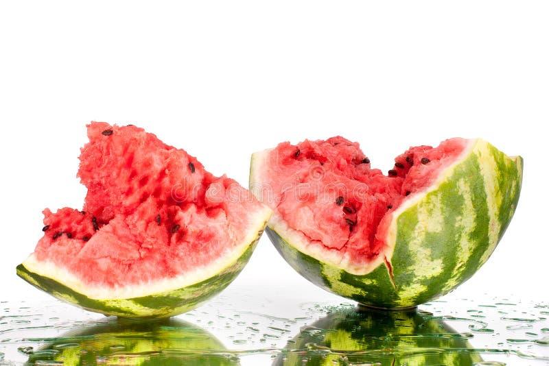 Vattenmelon halverar stycken med sprickor och vattendroppar på vit spegelbakgrund med reflexionen isolerat slut upp royaltyfri fotografi