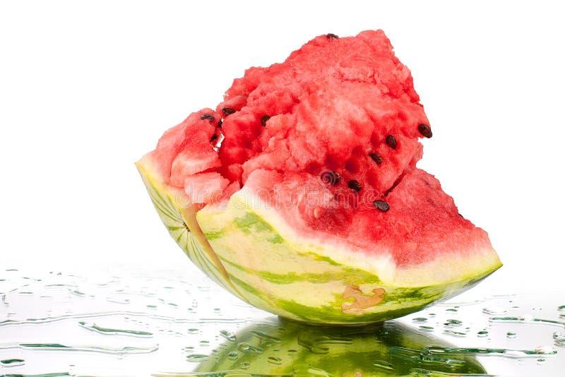 Vattenmelon stort stycke med sprickor och vattendroppar på vit spegelbakgrund med reflexion isolerat slut upp arkivfoto
