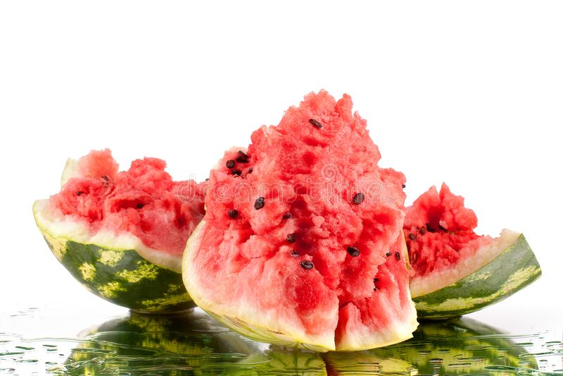 Vattenmelon tre stora stycken med sprickor och vattendroppar på vit spegelbakgrund med reflexion isolerat slut upp royaltyfria bilder