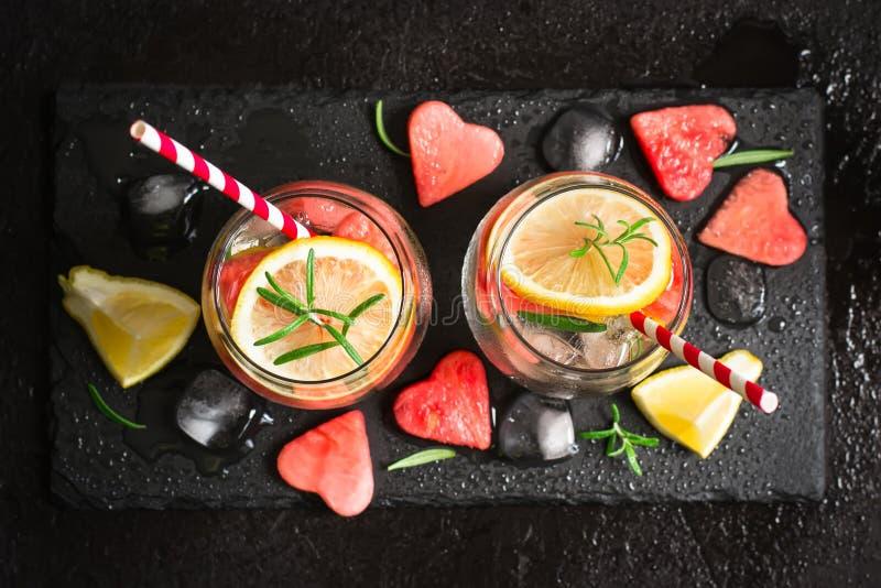 Vattenmeloncitroncoctail med stycken av vattenmelon i form av hjärta Begrepp för dag för valentin` s arkivfoto