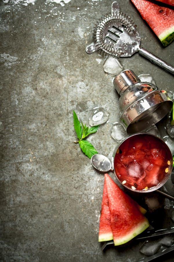 Vattenmeloncoctail med mintkaramellen och is i en shaker arkivfoto