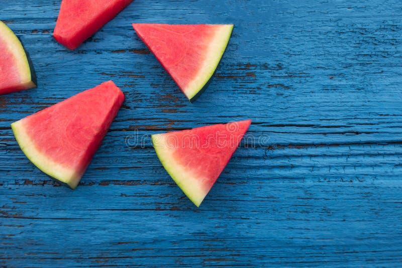 Vattenmelonfruktstycken på en blå lantlig wood bakgrund, lägenhet arkivfoton