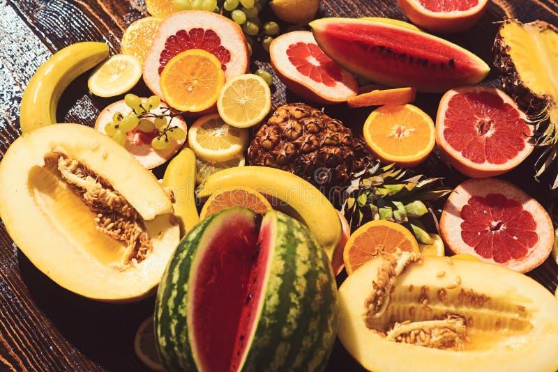 Vattenmelonmelon och banan med orange ananas citron med grapefrukt- och druvaorienteringen Nya frukter på trätabellen royaltyfria bilder