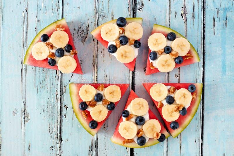 Vattenmelonpizza med bananer, blåbär och yoghurt på blått trä fotografering för bildbyråer