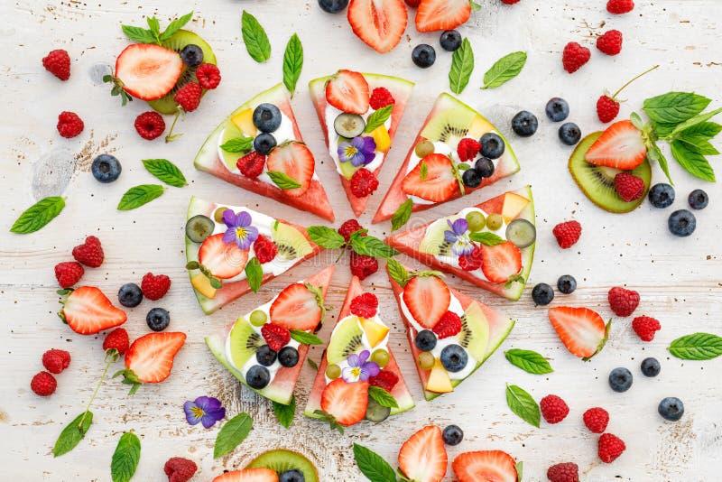 Vattenmelonpizza med olika nya frukter med tillägget av gräddost, mintkaramellen och ätliga blommor En läcker frukt- efterrätt royaltyfri fotografi