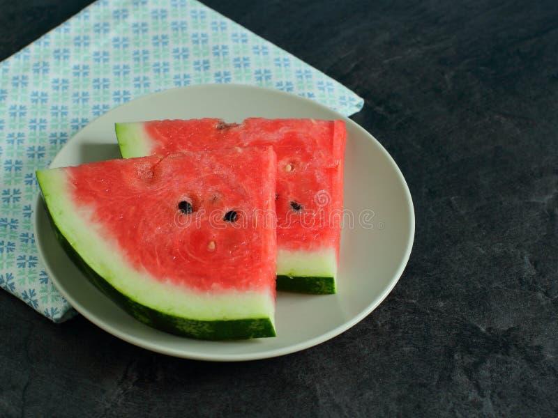 Vattenmelonskivor på en lantlig platta royaltyfria bilder
