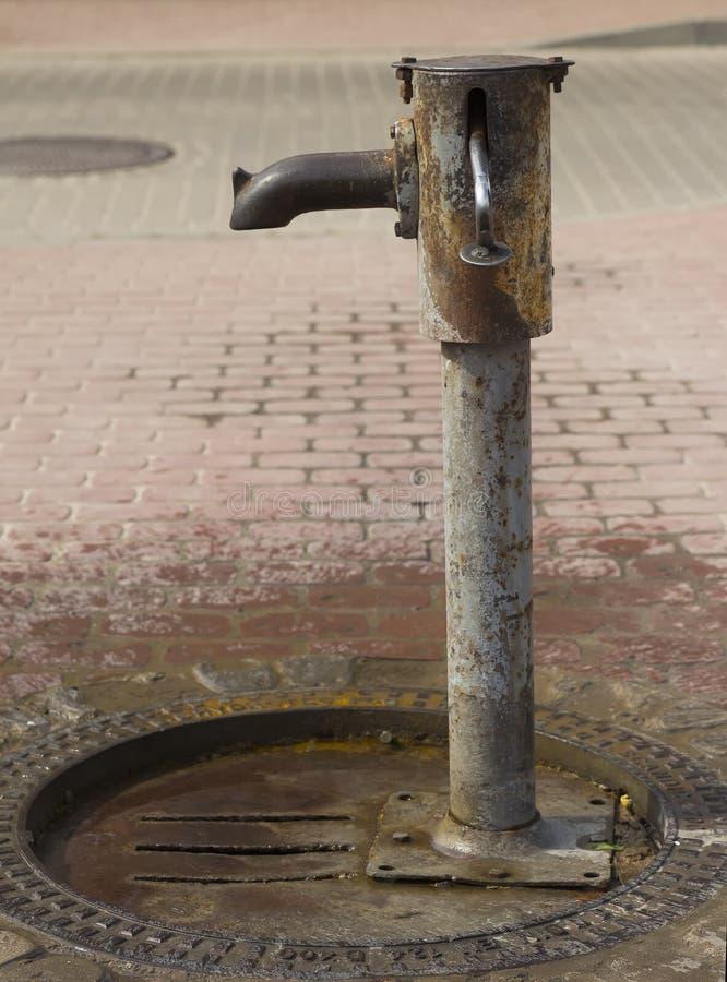 Vattenpump på gatatvärgatorna, liten stad royaltyfri bild