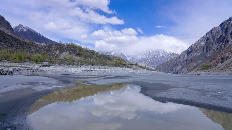 vattenreflexionen av berg som täckas med vit, fördunklar i Hunza royaltyfri fotografi