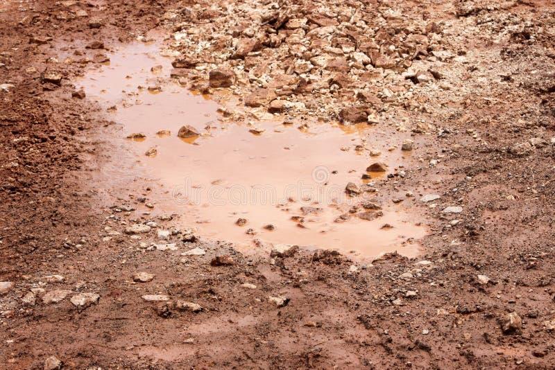 Vattenskovel på gatan efter fallande regn Väg efter regn Smutsig pöl på vägen efter regn Grusväg med leriga pölar royaltyfria bilder