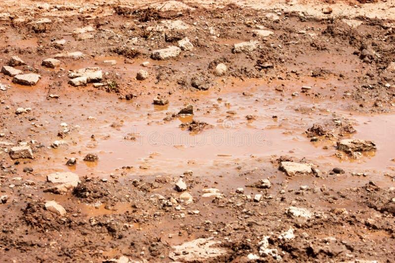 Vattenskovel på gatan efter fallande regn Väg efter regn Smutsig pöl på vägen efter regn Grusväg med leriga pölar royaltyfria foton