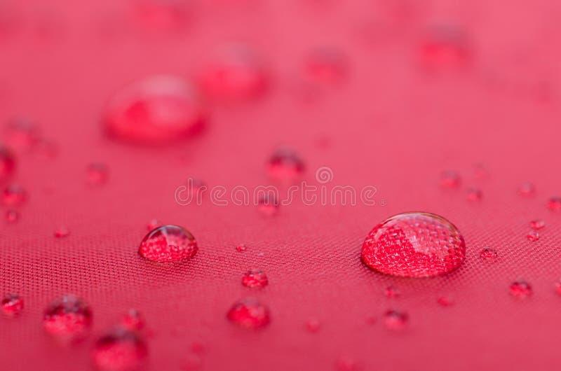 Vattensmå droppar är på färgrikt vattentätt tyg för fiber arkivfoto