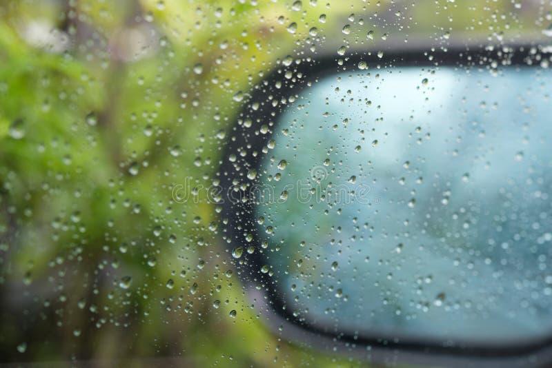 Vattensmå droppar på en vindruta royaltyfria bilder