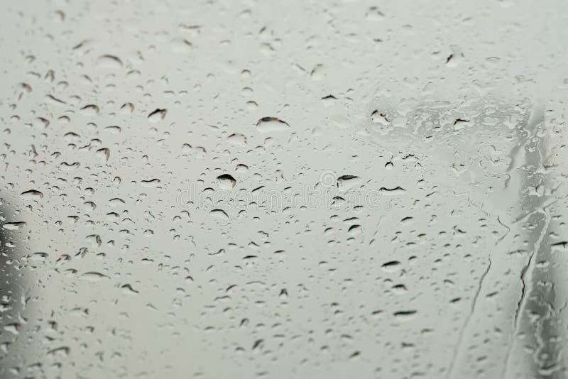 Vattensmå droppar på en vindruta arkivfoto