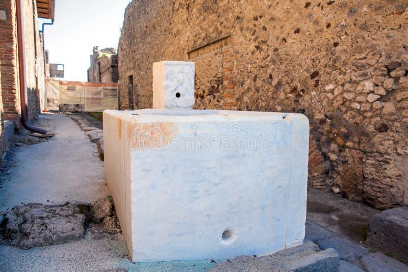 Vattenspringbrunn på gatorna av den forntida staden av Pompeii arkivbilder