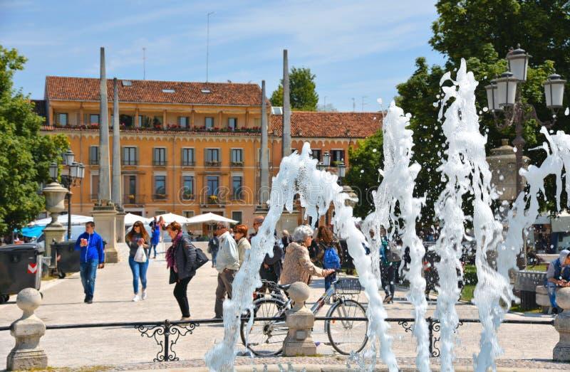 Vattenspringbrunnen, folket, färgrika byggnader, arkitektur, gräsplan parkerar och den gamla fasaden med blå himmel i Padua Venet fotografering för bildbyråer