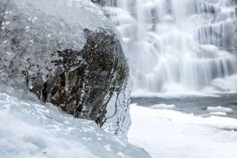 Vattenströmmen är fryste på stenen royaltyfri foto