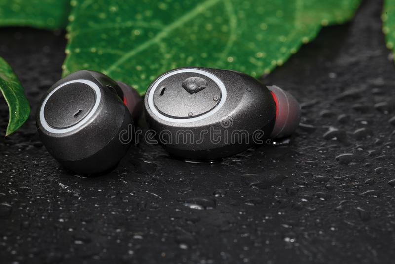 Vattentät hörlurar, svarta som hörlurar prydas med pärlor med vatten Hörlurar för att köra i regnet royaltyfria bilder