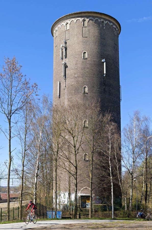 Vattentorn och cyklist i den holländska staden Heerlen arkivfoto