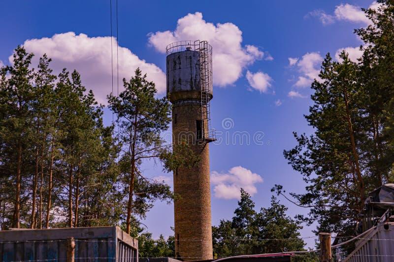 Vattentorn på en bakgrund av blå himmel med moln royaltyfria bilder