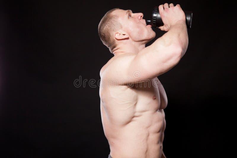 Vattnet för idrottsman nenkroppsbyggaredrinkar ut ur en shaker royaltyfri foto