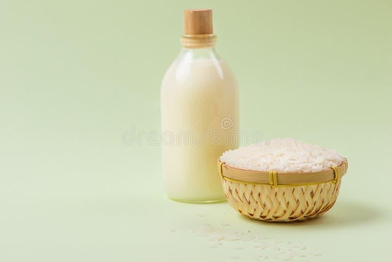Vattnet som rena ris som mjölkar ut i exponeringsglaset? och några grova ris i bambukorgar royaltyfri foto