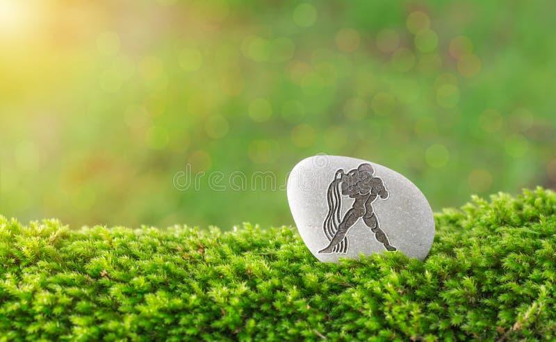 Vattumannenzodiaksymbol i sten royaltyfri foto