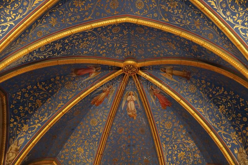 Vaulted ceiling with golden floral pattern on blue background and religious figures around the central vault stone royalty free stock images