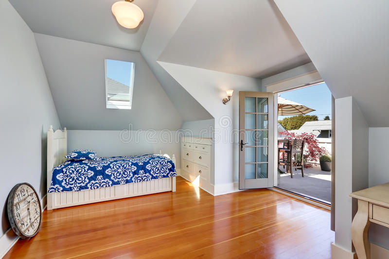 Vaulted ceiling kids bedroom in the attic with exit to the roof terrace. Vaulted ceiling kids bedroom in the attic with open door to the roof terrace. Northwest royalty free stock images