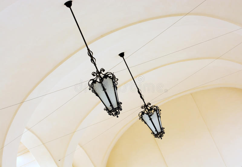 Vaulted ceiling with ornate iron lamps stock images