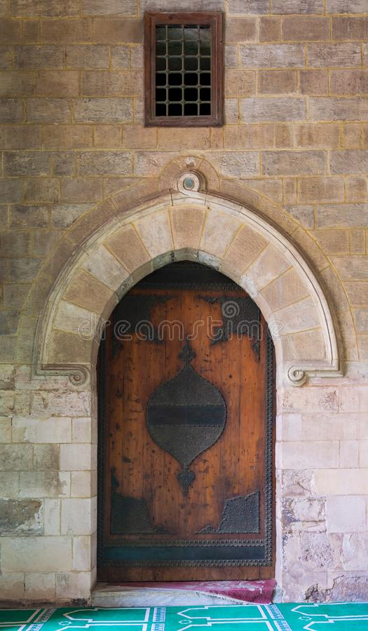 Vaulted closed decorated wooden grunge door in bricks stone wall. At public historic Al Moaayad Mosque, Cairo, Egypt royalty free stock photo