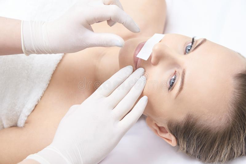 Vaxa kvinnabenet Sockerhårborttagning laser-serviceepilation Tillvägagångssätt för salongvaxkosmetolog royaltyfria bilder