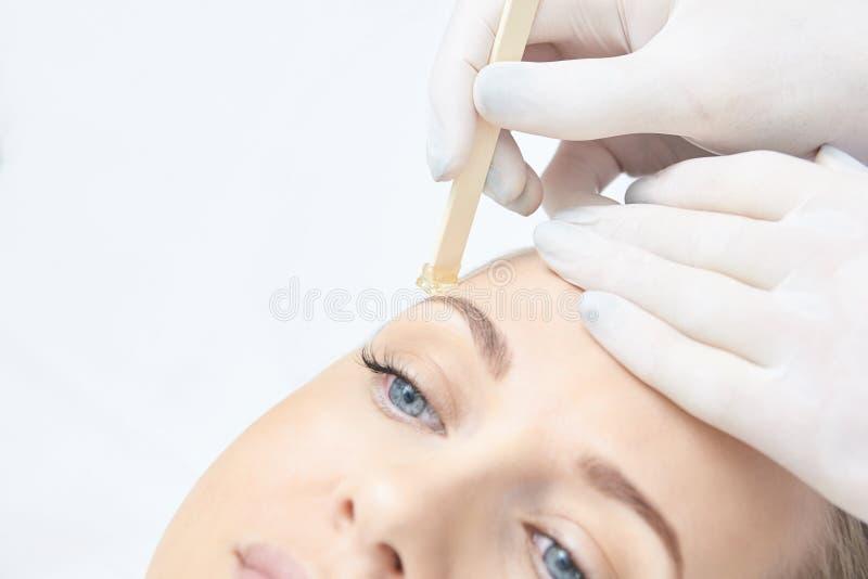 Vaxa kvinnabenet Sockerhårborttagning laser-serviceepilation Tillvägagångssätt för salongvaxkosmetolog arkivfoto