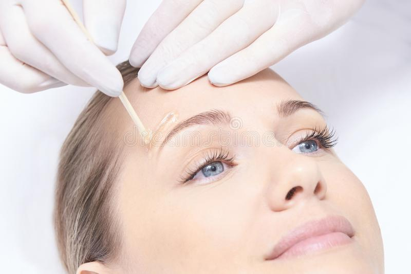 Vaxa kvinnakroppen Sockerhårborttagning laser-serviceepilation Tillvägagångssätt för salongvaxkosmetolog royaltyfri bild