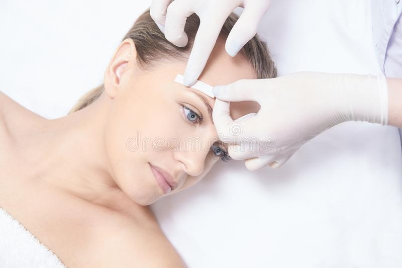 Vaxa kvinnakroppen Sockerhårborttagning laser-serviceepilation Tillvägagångssätt för salongvaxkosmetolog royaltyfria foton