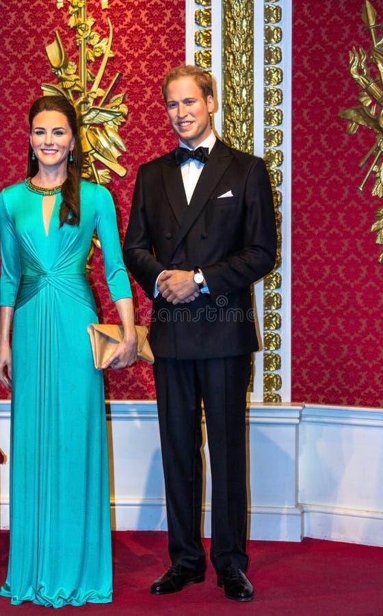 Vaxdiagram av prinsen William och Kate Middleton ses på skärm på museet för madamen Tussauds London royaltyfri foto