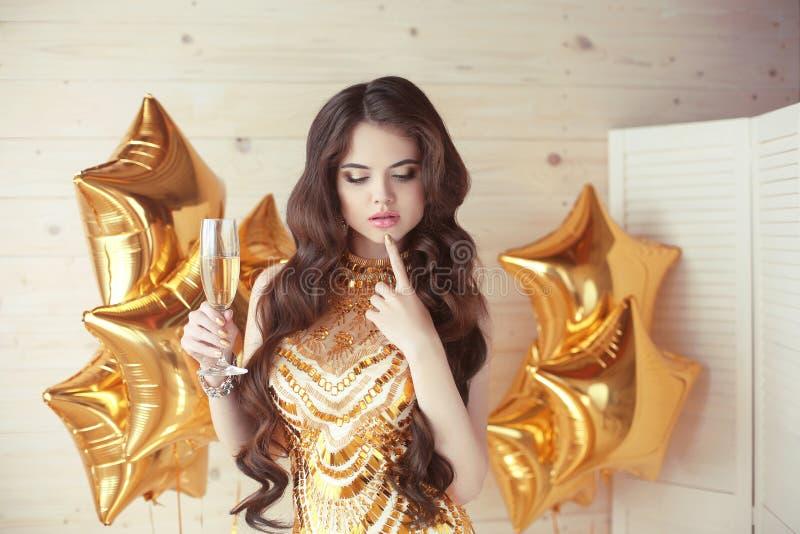 Vaya de fiesta la celebración, mujer joven magnífica en el pensamiento de oro del vestido fotografía de archivo libre de regalías